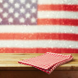 Empty wooden deck table with tablecloth over USA flag bokeh background. 4th of July celebration picnic background. Stock Image