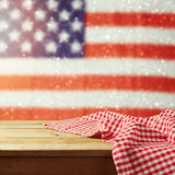Empty wooden deck table with tablecloth over USA flag bokeh background. 4th of July celebration picnic background. Ready for product display montage royalty free stock photo