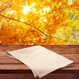 Empty wooden deck table with tablecloth. For product montage. Autumn landscape. Free space for your text stock photo