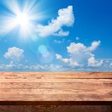 Empty wooden deck table with tablecloth. For product montage. Sunny Day, Blue Sky with Clouds Free space for your text Royalty Free Stock Images