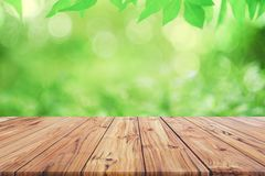 Empty wooden deck table top on green blurred abstract background from foliage background. Ready used us display or. Montage products design stock photography