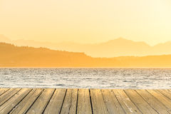 Empty wooden deck table top Ready for product display montage with sea when sunset background. Stock Photos