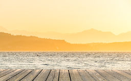 Empty wooden deck table top Ready for product display montage with sea when sunset background. Stock Photo