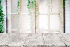 Empty wooden desk over blurred interior decoration background royalty free stock photo