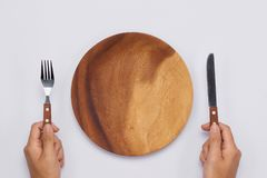 Empty wooden dish with knife and fork in hands. Top view.  royalty free stock image