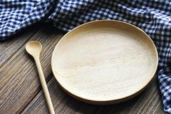 Empty wooden dish with spoon and tablecloth on table, Wooden kitchenware. Plate and spoon on wood background Royalty Free Stock Photo