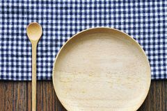 Empty wooden dish with spoon and tablecloth on table, Wooden kitchenware. Empty wooden dish with spoon and tablecloth on table, Wooden kitchenware Plate and Stock Image