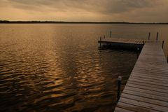 The empty wooden dock as the sun sets Stock Photo