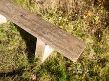 Empty wooden end of bench outside grass background Stock Photography