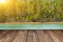 Empty wooden floor and blurred forest on water lake sunset  Stock Photos