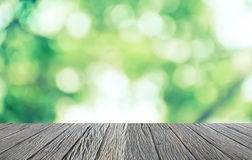 Empty wooden floor with green bokeh and sunlight. Beauty natural background Royalty Free Stock Photo