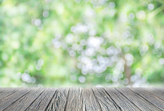Empty wooden floor with green bokeh and sunlight. Beauty natural background Royalty Free Stock Images
