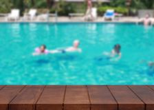 Empty wooden floor on pool. Tourists family swimming blurred bac. Kground. There is an empty space for productions Royalty Free Stock Photography