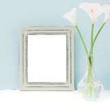Empty wooden frame and flowers in vase on table on blue background. mock up Stock Images
