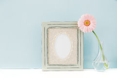 Empty wooden frame and flowers in vase on table on blue background. mock up Royalty Free Stock Image