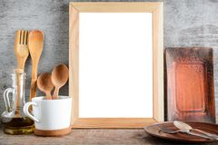 Empty wooden frame and kitchen accessories on the table stock photography