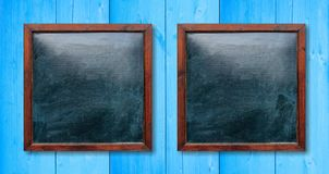 Empty wooden frames on the wall. Blackboards inside and light blue background, space for text. Blank wooden frames on the wall. Blackboards inside and light stock photo