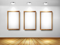 Empty wooden frames on wall with spotlights and wo Royalty Free Stock Photo