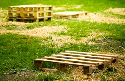 Empty wooden pallets on green grass Stock Photography