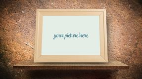 Empty wooden photo frame on brown surface. Empty wooden photo frame on grungy brown surface Stock Photo