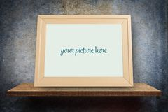 Empty wooden photo frame on grungy gray wall background Royalty Free Stock Image