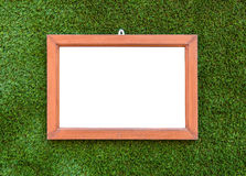 Empty Wooden photo frame hang on Artificial Green grass. Royalty Free Stock Photo