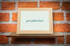 Empty wooden photo frame mock up on brick Royalty Free Stock Photography