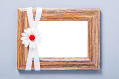 Empty wooden photo frame with white ribbon and flower. Empty wooden photo frame with white ribbon and flower on gray wall. Save clipping path Royalty Free Stock Photos