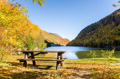 Empty Wooden Picnic Table near the Shore of a Mountain Lake. Empty Wooden Picnic Table on a Lake Surrounded By Wooded Mountains on a Sunny Autumn Day. Adirondack Stock Photos