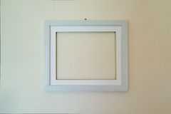 Empty wooden picture frame mounted on the wall Royalty Free Stock Photos