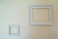 Empty wooden picture frames mounted on the wall. With wallpaper behind Royalty Free Stock Photography