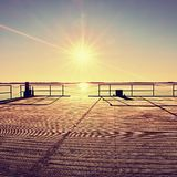 Empty wooden pier at beautiful colorful morning. Tourist wharf in sea bay. Stock Photo
