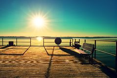 Empty wooden pier at beautiful colorful morning. Tourist wharf in sea bay. Royalty Free Stock Photos