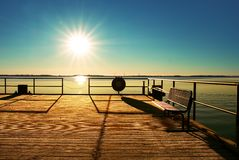 Empty wooden pier at beautiful colorful morning. Tourist wharf in sea bay. Royalty Free Stock Images