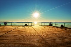 Empty wooden pier at beautiful colorful morning. Tourist wharf in sea bay. Stock Images