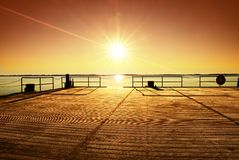 Empty wooden pier at beautiful colorful morning. Tourist wharf in sea bay. Stock Photos