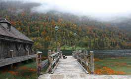 An empty wooden pier by beautiful lakeside on a misty foggy morning. ~ Gloomy autumn scenery of Konigssee (King's lake) in Bavaria, Germany royalty free stock photos