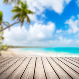 Empty wooden pier over blurred tropical beach Royalty Free Stock Photography