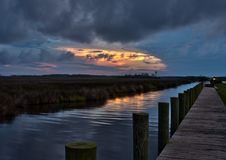 Fishing pier and wetlands at at dusk. An empty wooden pier by the wetlands at dusk, located on the calm waters of the Albermarle Sound at the Outer Banks of Stock Images