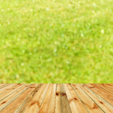 Empty wooden planks with green leaves bokeh background Royalty Free Stock Photo