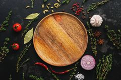 Empty wooden plate and frame of spices, herbs and vegetables on a dark stone background. Top view, flat lay. Thyme, chili, peppercorn, tomato, garlic, red onion royalty free stock photography