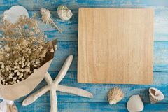 Empty Wooden plate and Sea shells and starfish on a blue Rustic Stock Photography