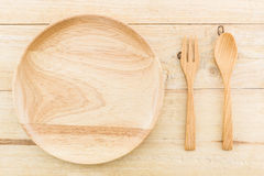 Empty wooden plate and spoons, forks. Royalty Free Stock Photography