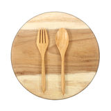 Empty wooden plate and spoons, forks on white background Stock Photography
