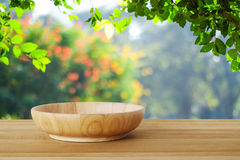 Empty wooden plate on table over blur trees with bokeh backgroun Royalty Free Stock Image