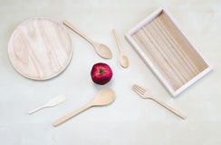 Empty wooden plate, wooden tray, wooden spoon, wooden fork, wooden tea spoon, wooden scoop and Orange in a basket. Stock Image