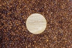 Empty wooden round board in roasted coffee beans. Round wooden board lies n the roasted coffee beans as background royalty free stock photography
