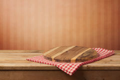 Empty wooden round board on tablecloth over red wall background for product montage. Display stock photos
