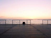 Empty wooden sea bridge. The way to see the sunrise above sea horizon. Texture selective focus Stock Image