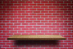 Empty wooden shelf on brick wall royalty free stock image